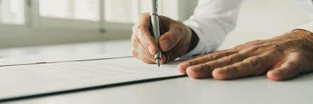 Foto de Wide low angle view image of businessman signing a document with silver ink pen. - Imagen libre de derechos