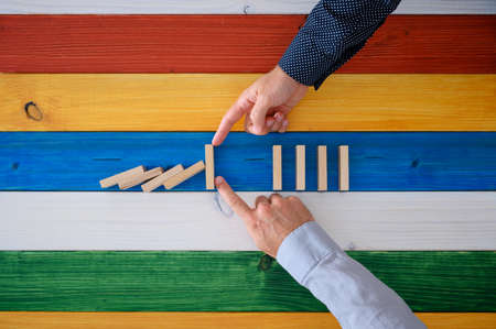 Two male hands working together to stop dominos from collapsing in a conceptual image. Over colorful background of wooden planks.