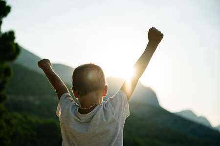 Photo pour View from behind of a young child with his arms raised high in the air welcoming the rising morning sun. - image libre de droit