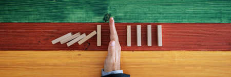 Wide view image of businessman hand stopping dominos from collapsing in a conceptual image. Over colorful background of wooden boards.