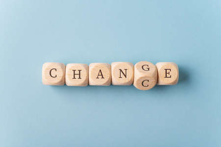 Foto de Word Change spelled with wooden dices with the dice carrying letter G turning to spell the word Chance. - Imagen libre de derechos