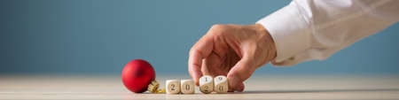 Photo pour Wide view image of red christmas bauble next to a 2019 sign on wooden cubes with male hand turning last two number to 2020. - image libre de droit