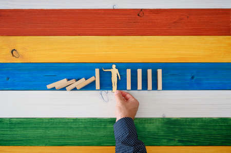 Top view of male hand placing paper cut silhouette of a man to intervene and prevent dominos from collapsing. Over colorful background of wooden boards.