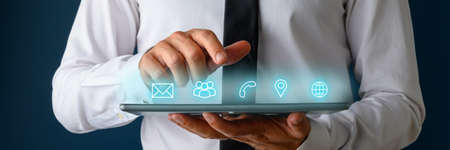 Photo pour Front view of businessman using digital tablet with icons of contact, communication and location glowing on an interface above the device. - image libre de droit