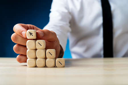 Photo pour Businessman making a stack of wooden dices assembling an arrow shooting upwards in a conceptual image. Over navy blue background. - image libre de droit