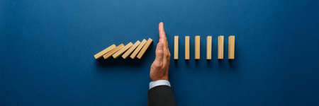 Foto de Wide view image of businessman hand stopping collapsing dominos in a conceptual image. Top view over navy blue background. - Imagen libre de derechos