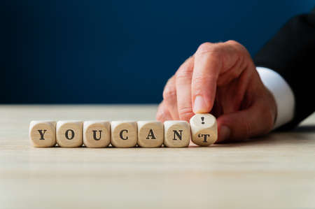 Photo pour Hand of a businessman changing a You cant sign on wooden cubes in to a You can! by flipping the last dice. - image libre de droit