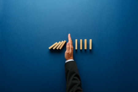 Photo pour Top view  of businessman hand stopping falling dominos in a business crisis management conceptual image. - image libre de droit