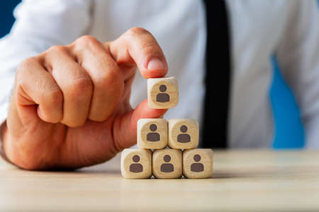 Foto de Business executive stacking wooden dices  with people icons on them in a pyramid shape in a conceptual image. - Imagen libre de derechos