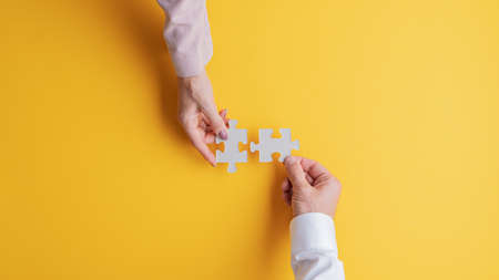 Foto de Top view of male and female hands joining two matching puzzle pieces together in a conceptual image. Over yellow background. - Imagen libre de derechos