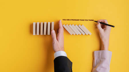 Top view of businessman stopping collapsing dominos with his hand and his female partner writing a You are stronger than you think sign next to him. Over bright yellow background.