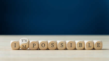 Photo pour Word impossible spelled on wooden dices with the second one turning to spell the Its possible sign. - image libre de droit
