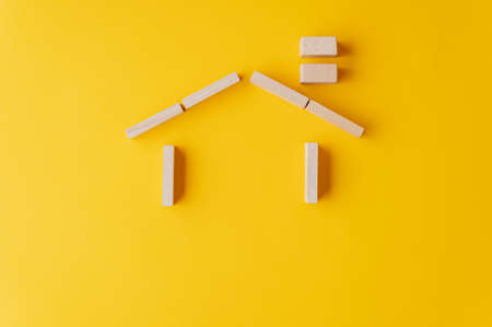 Photo pour House made of wooden pegs on yellow background in a conceptual image of insurance or ownership. With copy space. - image libre de droit