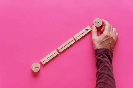 Male hand placing wooden pegs and circles to form a diagram with arrow pointing from word Start to Goal in a conceptual image of personal aspirations. Over pink background.