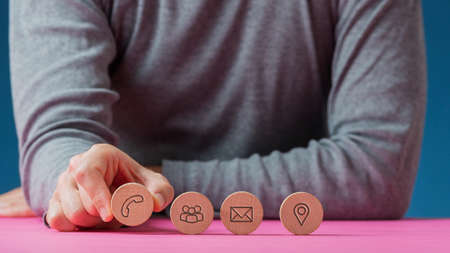 Photo for Front view of a man placing four wooden cut circles with contact and communication icons on them in a row on pink desk. - Royalty Free Image