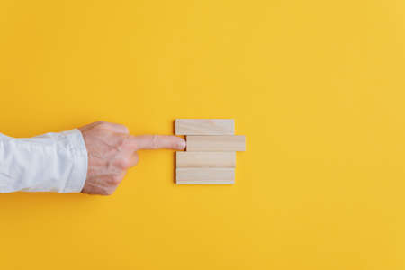 Photo pour Businessman pushing the second peg from the top out of the stack of them in a conceptual image. Over yellow background. - image libre de droit