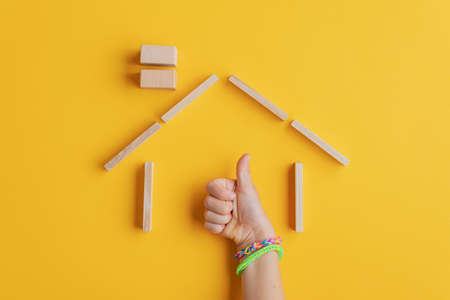 Photo pour Childs hand wit colorful bracelets making a thumbs up sign holding his hand inside a house made of wooden pegs. Over yellow background. - image libre de droit