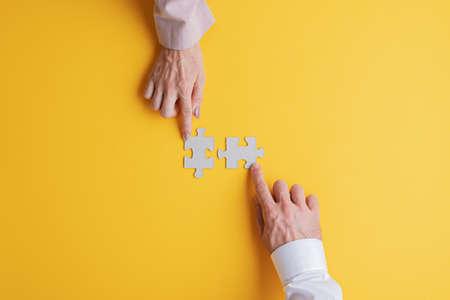 Photo pour Hands of a businessman and businesswoman each placing one blank puzzle piece over yellow background. - image libre de droit