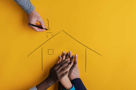 Photo pour Hand of a mother and three children of caucasian and black ehnicity in a house hand drawn by the father. Over yellow background. - image libre de droit