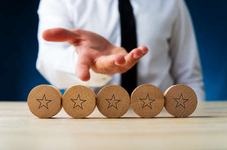 Photo for Hand of a businessman presenting five wooden cut circles with stars on them in conceptual image of luxury and wealth. - Royalty Free Image