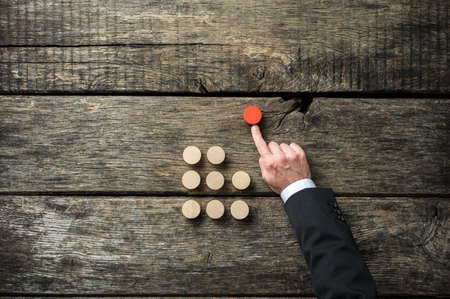 Photo for Hand of a businessman pushing red wooden cut circle out of the crow of others in a conceptual image of self initiative and determination. - Royalty Free Image