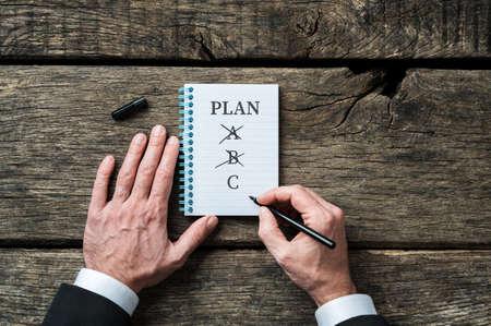 Photo pour Businessman considering various future plans, choosing between A, B and C. - image libre de droit