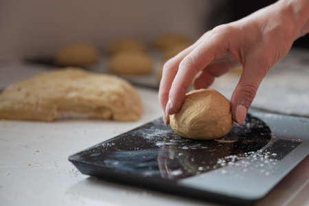 Foto für Closeup of female hand weighing home made pastry dough ball. - Lizenzfreies Bild