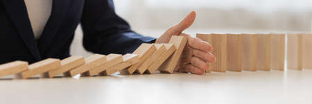 Wide view image of hand of businesswoman interrupting collapsing dominos in a conceptual image of preventing financial and market depression.