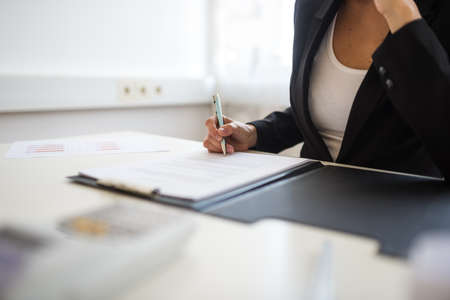 Photo for Closeup view of businesswoman sitting at her desk signing a document or contract in a folder. - Royalty Free Image