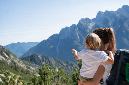 Photo for Young mother holding her toddler daughter  looking at beautiful view of mountains as they hike together on a sunny day. - Royalty Free Image