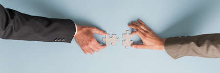 Photo pour Wide view image of male and female hand joining two blank matching puzzle pieces. - image libre de droit