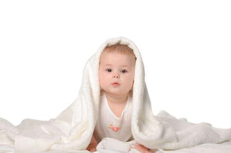 Foto de The baby under a towel. Age of 8 months. It is isolated on a white background - Imagen libre de derechos