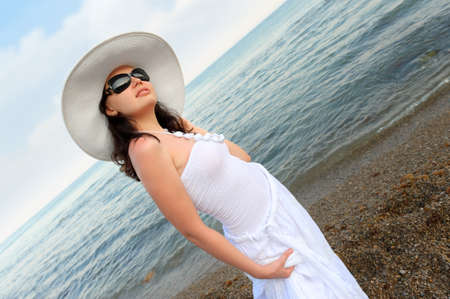 The woman on seacoast. In sun glasses, a sundress, a hat.