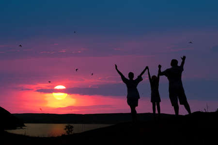 The family from three persons welcomes the sunset sun.