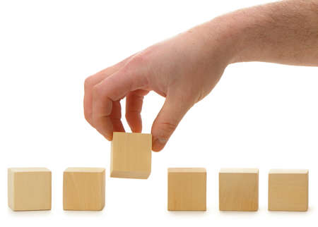 Photo pour The hand establishes a wooden cube in row. It is isolated on a white background - image libre de droit