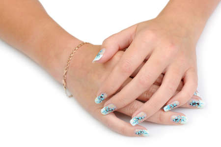 Female hands with manicure close up. Drawing of a branch with blue flowers. It is isolated on a white background.の写真素材