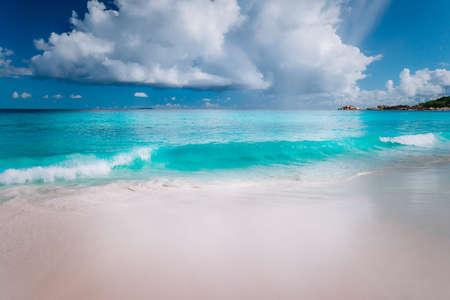 Photo pour Beautiful white wave rolling towards tropical sandy beach. Gorgeous fluffy clouds above blue sea. Seychelles Grand Anse, La Digue, Seychelles. - image libre de droit