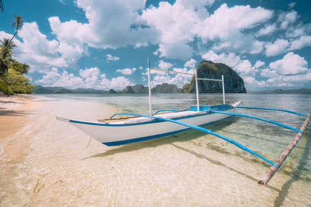 Photo pour El Nido, Palawan, Philippines. White banca boat on sandy beach with crystal clear water ready for island hopping trip. Amazing Pinagbuyutan island in background. Beautiful landscape scenery - image libre de droit