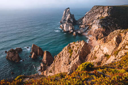 Praia da Ursa Beach with rocks in foreground lit by sunset light. Surreal scenery of Sintra, Portugal. Atlantic Ocean coastline landscape.