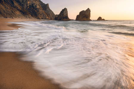 Portugal Ursa Beach. Sunset light reflection in white wave rolling towards sandy beach with silhouette of sea stacks in background.
