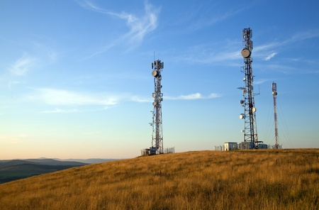 communication towers on top of hill with blue sky background