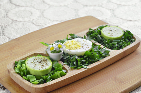 Finally chopped different greens with egg and raw zucchini in a wooden plate. Selective focus