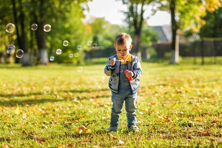 Photo pour A little boy in denim clothes blows bubbles in the autumn park. - image libre de droit
