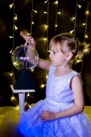 Photo for Cute little Child girl holding witch crystal ball with lightning and electricity over dark background with garlands bokeh - Royalty Free Image