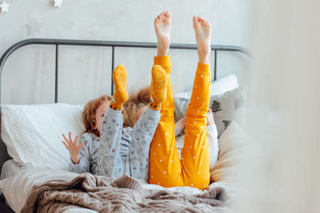 Foto per Little pretty brother and sister in pajamas lying in bed, cozy morning, focus on legs - Immagine Royalty Free