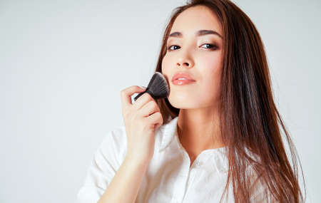 Foto per Make up brush kabuki in hand of smiling asian young woman with dark long hair on white background - Immagine Royalty Free
