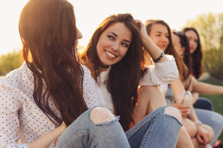 Photo for Group of young happy girls friends enjoy life on summer city street, sunset background - Royalty Free Image