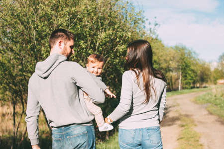 Photo pour Happy family with cute baby boy walking on road outdoors, sensitivity to the nature concept - image libre de droit
