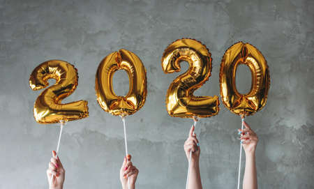 Foto de The woman hands holding 2020 numbers balloons on the grey concrete wall background. New Year party with friends, corporate - Imagen libre de derechos