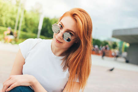 Photo for Attractive redhead smiling girl in round sunglasses in casual clothes sitting on street in the city - Royalty Free Image